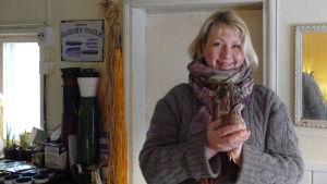 Sara Randström i sin bastukammare där hon odlar tulpaner. Håller en vaktel i sina händer.