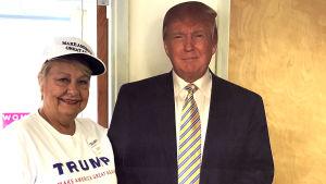 Barbara Dawson poserar bredvid en Donald Trump-figur i kartong i repulikanernas kampanjlokal.