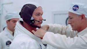 Buzz Aldrin får dräkten justerad.