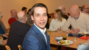 Henrik Wickström sitter vid ett bord tillsammans med en drös andra.