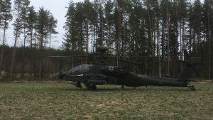 En amerikansk Apache-helikopter på ett fält i den estniska skogen.