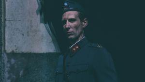 Touko Laaksonen (Pekka Strang) i uniform, ser rakt in i kameran.