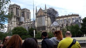 På bilden ses Notre-Dame katedralen inplastad och omgiven av byggställningar.