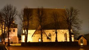 Borgå domkyrka upplyst av lampor i mörkret. Det är en stor vit stenbyggnad med mörkt spåntak.