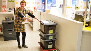 En kvinna står vid stora plastlådor. Hon pekar mot lådorna. De innehåller böcker, med det ser man inte.