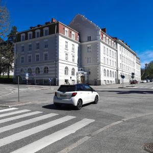 En vit byggnad bakom en korsning. Det är en solig dag. En bil kör genom korsningen.