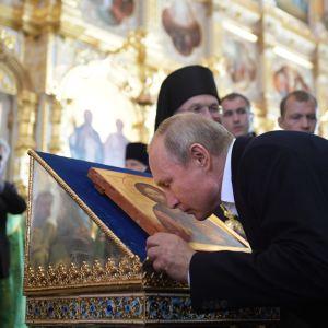Vladimir Putin kissing an icon