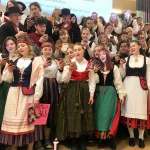 Kansallispukuihin pukeutuneet abit laulavat