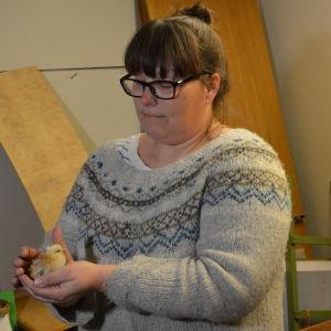 En dam i grå tröja och glasögon håller en liten gul kyckling i sina händer.