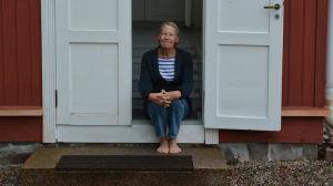 Kvinna sitter i dörröppningen till sommarvilla.