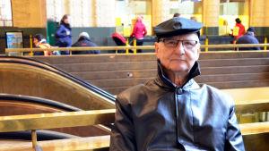 Timo Mäcklin sitter på en bänk i Helsingfors Centralstation.