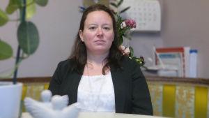 Johanna Sjöberg sitter i soffan i sin begravningsbyrå