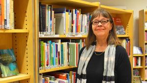 Bibliotekschefen Margareta Kull-Poutanen ser nöjd ut. Står framför bokhyllor.