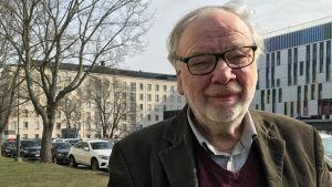 En man med glasögon och grått hår tittar in i kameran. Han står på en gräsmatta och bakom honom syns bilar och träd.
