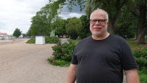 Magnus Boberg står på en strand med buskar och träd i bakgrunden. Han ler och har glasögon.