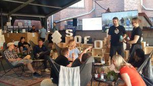 Unga vuxna sitter i säckstolar och solstolar på en business- och framtidsfestival.