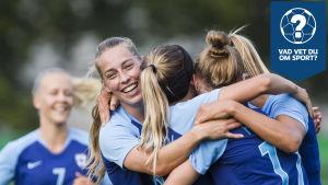 Några blåklädda spelare i Finlands landslag firar ett mål genom att kramas med varandra.
