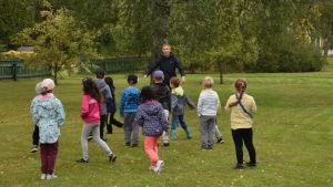 En kvinna leder en lek med en massa små barn som springer på en grön gräsmatta.