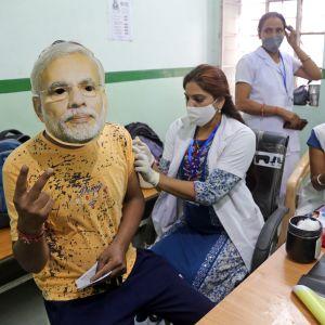 Terveydenhoitaja antaa koronarokotteen intialaiselle henkilölle.