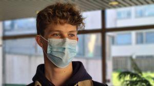 En man med munskydd på tittar snett ut mot kameran.
