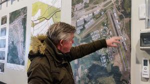 En man i dunjacka pekar på en kartskiss som finns på en vägg.