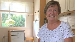 En äldre dam som sitter i sitt kök.