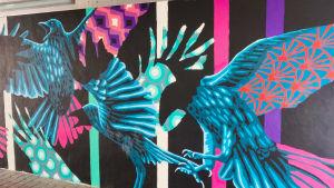 En väggmålning med stora fåglar i svart, blått och ljusrött.