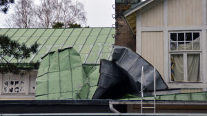 Ett plåttak på en gammal byggnad. På taket ligger en stor bit plåt som blåst bort från en annan del av taket.