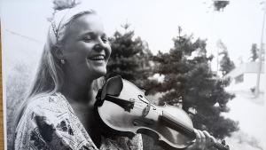 Svartvitt foto av Raakel som leende håller i fiolen.