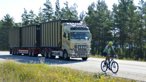 En cyklist cyklar på en riksväg. Bakom cyklisten kör en stor långtradare.