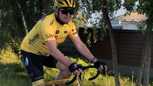 Christer Holmlund cyklar på en cykel. Han har färgglada cykelkläder på sig.