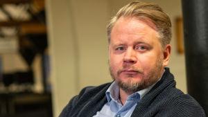 Ett porträttfoto av biträdande professor Jan Antfolk i Åbo Akademis bibliotek.