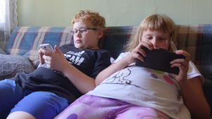 Två barn, en flicka och en pojke sitter i en rutig soffa och spelar på sina mobiltelefoner. Pojken har rött hår och glasögon och flickan har pannlugg och en vit skjorta med en bild av hunden Snoopie.