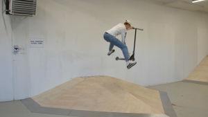 Erik Kinnunen flyger i luften med sin sparkcykel.