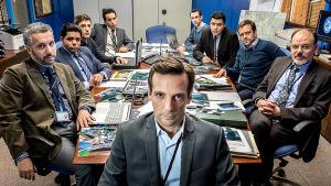 Le bureau, vakoojaverkosto -sarjan miehet istuvat pöydän äärellä ja katsovat kameraan.