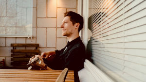 Musikern Månskensbonden sitter på sin balkong med gitarr i famnen.