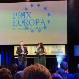 Lavalla mies seisoo palkinnon kanssa ja nainen haastattelee häntä. Molemmat hymyilevät.