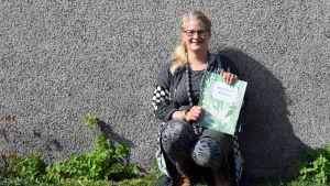 """Illustratören Anni Pöyhtäri med sin bok """"Hemulin Kasvio""""."""