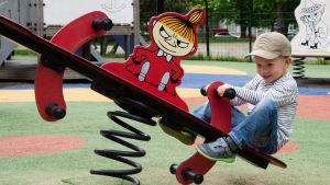 John är glad och gungar på en röd Lilla My fjädergunga