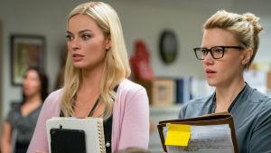 Kayla och hennes kollega står och lyssnar på feedback under ett möte.