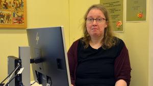 En kvinna sitter framför en dator. Hon tittar in i kameran.