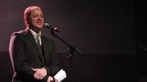 En man som står på en scen iklädd kostym.