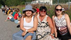 Sandra, Laura och Karin Veijola sitter i solen.