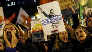 Personer håller i plakat och protesterar i Tyskland.
