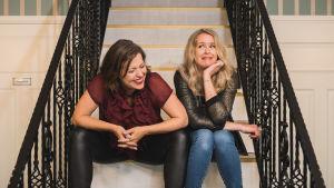 Eva Frantz och Hannah Norrena sitter i en trappa.