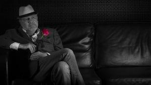 Svartvit bild på Mårten Holm i kavaj och vit hatt i mörk lädersoffa med röd ros i kavajuppslaget.