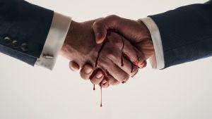 Kädenpuristus, jonka kämmenien välistä tihkuu verta.