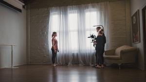 Fotografen Rasmus Tåg och regissören Maria Seppälä står i ett rum tillsammans med en dansös i Taideruukki i Kuusankoski.