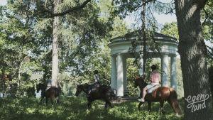 Tre ryttare rider förbi en vit tempelliknande byggnad i en lummig lövskog.