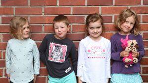 Fyra barn i dagisåldern står framför en tegelvägg.